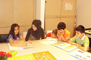 Bild Junge Frau sitzt mit 4 Kindern um einen Tisch und gibt Hausaufgabenhilfe