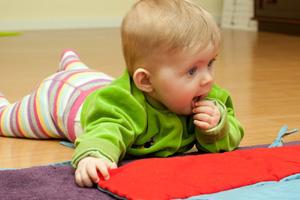 Bild Baby krabbelt nachdenklich auf dem Fussboden vor einer Decke