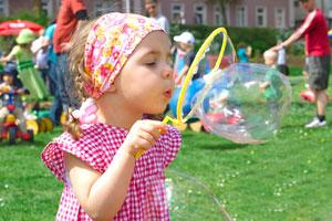 Bild Kleinkind bläst auf Spielplatz eine Seifenblasse auf, im Hintergrund andere spielende Kinder