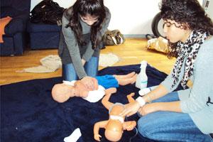 Bild: 2 jugenliche Mädchen üben an Puppen während ihrer Ausbildung zum Babysitter