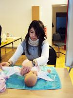 Bild: jugenliches Mädchen übt an einer Puppe während ihrer Ausbildung zum Babysitter