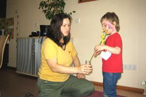 Bild Kind steckt eine selber gebastelte Muttertagsblume in ein Vase, die seine Mutter hält.