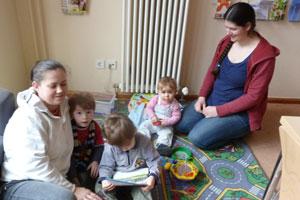 Bild zwei Mütter spielen mit ihren Kleinkindern auf einem Fußboden