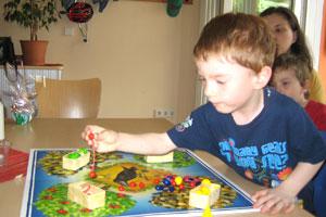 Bild Kind spielt am Tisch ein Brettspiel