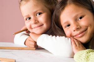 Bild 2 Kinder beim malen, lächeln mit Kopf auf die Hände gelegt in die Kamera