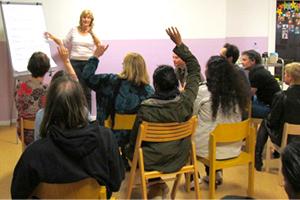 Bild Teilnehmer eines Vortrags folgen den Ausführungen auf einer Leinwand