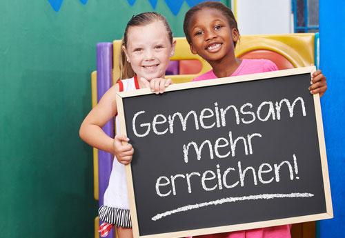 Foto: 2 Kinder halten eine Tafel mit Aufschrift Gemeinsam mehr erreichen