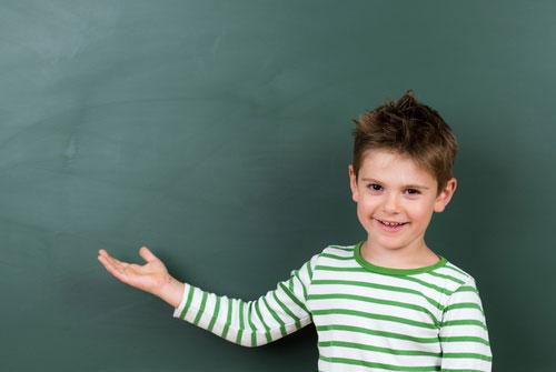 Foto: Kind steht mit ausgestreckter Hand und leicht angewinkeltem Arm nach links und Blick zum Betrachter
