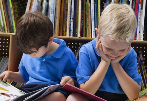 Foto: 2 Kinder mit blauem T-Shirt sitzen lesend auf dem Boden vor einem Bücherregal