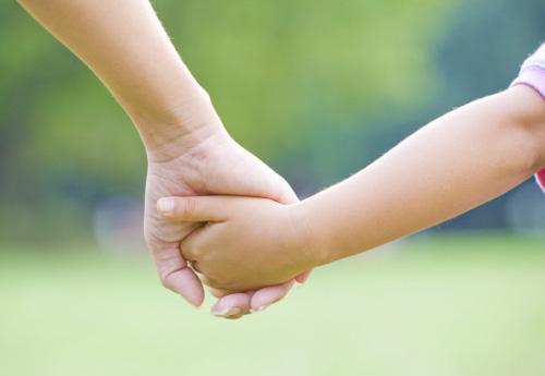 Foto: eine Erwachsenenhand von links hält eine Kinderhand von rechts