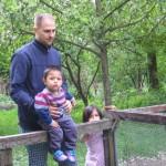 Bild: Vater schaut mit seinen beiden Kindern in den Kanichenstall. Dabei sitzt der Junge auf dem Zaun und der Vater hält ihn von hinten fest.