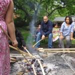Bild: Eltern und Kinder beim Stockbrotbacken um ein Lagerfeuer herum.
