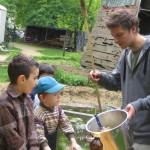 Bild: Jugendlicher Erzieher zeigt Kindern die Herstellung des Teiges für das Stockbrot
