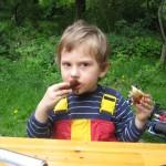 Bild Kind isst Stockbrot mit Nusscreme an einem Tisch