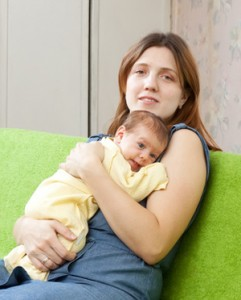 Bild Mutter mit Baby auf dem Bauchliegend und im Arm auf grünem Sofa