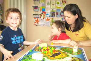 Bild: Mutter spielt mit ihren Kindern am Tisch ein Brettspiel