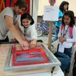 Bild: Siebdruckerei - ein Mädchen und der Drucker stellen einen Siebdruck her