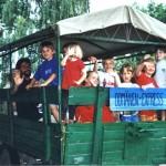 Bild: Mehrere Kinder winken von einem grünen Traktoranhänger