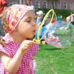 Bild Mädchen blässt eine Seifenblase auf einem Spielplatz, Kinder im Hintergrund