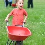 Bild Kleiner Junge läuft mit der Schubkarre