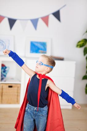 """Bild Kleiner Junge spielt """"Superman"""" in selbst gemachter Verkleidung mit rotem Umhang und Brille"""