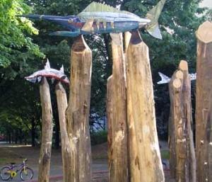 Bild Bunte Holzfische sind an den Spitzen dicker Holzpfälen aufgespießt