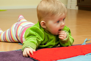 Bild Baby spielt bauchliegend auf dem Fußboden