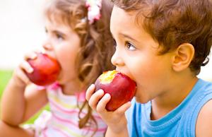 Bild: ein Junge und ein Mädchen essen jeweils einen großen roten Apfel
