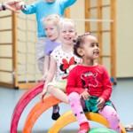 Bild Vier kleine Mädchen turnen auf Geräten in einer Turnhalle