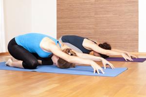 Bild Zwei Frauen machen eine Yogaübung auf dem Boden einer Turnhalle
