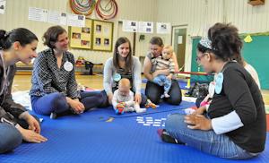 Bild Junge Mütter sitzen mit ihren Babys im Kreis und machen Sprachübungen