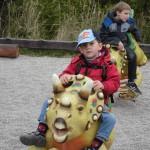 Bild - Kind reitet auf einer Urzeittier-Attrappe auf dem Spielplatz