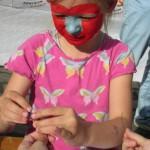 Bild - Kind mit bemaltem Gesicht bastelt eine Halskette