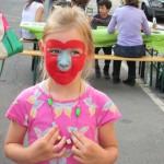 Bild - Kind mit bemaltem Gesicht und selber gebastelter Halskette