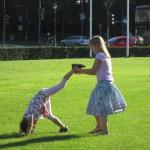 Bild - Zwei Mädchen spielen Siegessäule auf dem Rasen davor