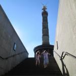 Bild - Blick auf die Siegessäule von unten aus der Unterführung, zwei Mädchen auf der Treppe der Unterführung davor