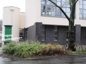 Bild: Eingangsbereich im Hintergrund. Strasse mit Mittelstreifen und Baum im Vordergrund.