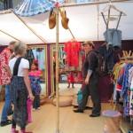 Bild: Auf dem Kleiderbasar probieren zwei Mädchen Kleidung an, unterstützt von der Mutter und dem Händler.