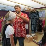 Bild: Auf dem Kleiderbasar probiert ein Mädchen ein Kopftuch, unterstützt vom Händler. Ein anders Kind steht im Vordergrund.