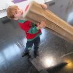 Bild: Junge versucht mit einem übermannsgroßen Buntstift auf dem Fußboden zu schreiben