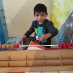 Bild: Junge lernt an einem Abakus (Rechenhilfsmittel mit Kugeln)