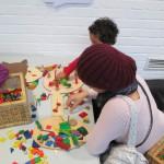Bild: zwei Kinder spielen mit buntem Holzfiguren auf eunem Tisch