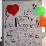 """Bild: Flipchart mit Schriftzug """"Herzlich Willkommen"""" und vielen Unterschriften der Anwesenden"""