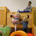 Bild: auf der Kletterburg. Zwei Kinder klettern nach oben und eines schaut von oben herunter.