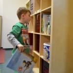 Bild: Kind steht vor Bücherregal, mit einem Buch in der rechten Hand und schaut auf andere Bücher im Regal.