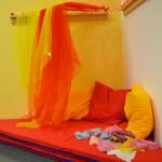 Bild: in einer Ecke des Raumes liegen rote Matratzen mit bunten Kissen und darüber herabhängenden Tücher