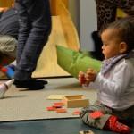 Bild: kleines dunkelhäitiges Kind spielt mit Holzkarten auf dem Fußboden. Im Hintegrund Füße und Beine von Kindern und Erwachsenen