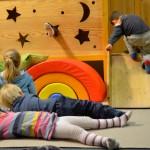 Bild: vor der Kletterburg. Kinder liegen auf dem Fußboden. Andere klettern auf der Burg.