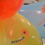 Bild: zwei Luftballons mit dem Logo des Familienzentrums - Schriftzug und Blume