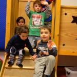 Bild: auf der Kletterburg. Mehrere Kinder winken.